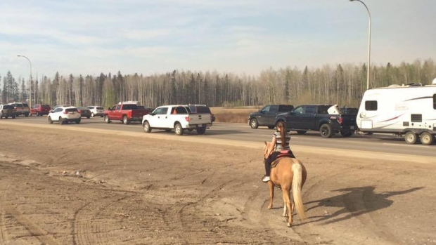 Young girl riding her horse alongside bumper-to-bumper traffic